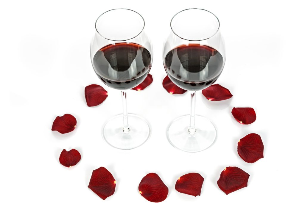 Two wine glasses with red wine surrounded by rose petals on a white background